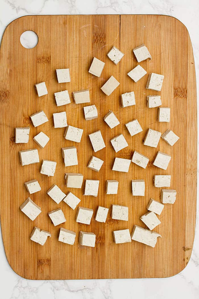 chopping up tofu into cubes
