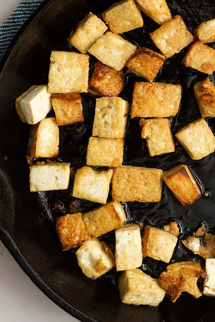 frying tofu in a black pan